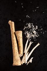 Horseradish root and grated horseradish on black background.