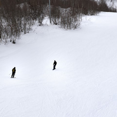 Skier and snowboarder on ski slope at gray winter day