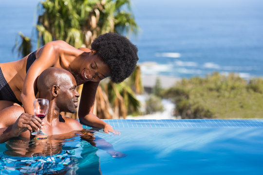 Romantic African Couple Relaxing by Pool with Ocean in Background and Glass of Wine