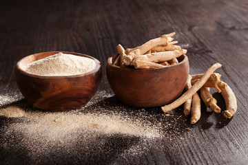 Ashwagandha root and powder in wooden cups on dark background.