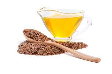Raw flax seeds in wooden spoon and linseed oil in glass gravy boat isolated on white background. Full depth of field stacked image.