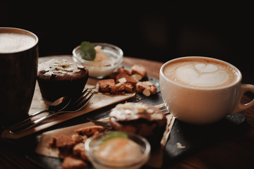 Close up food image of cup of coffee and dessert on the wooden table background in cafe. Trend warm toning. Photo with a small depth of field