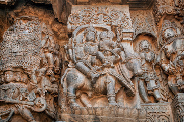 Shiva and his wife parvati sitting on cow, carved wall of 12th century historical Hoysaleswara Hindu temple, Halebidu, India