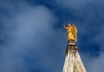 Golden angel statue among clouds, at the top of Saint Mark Bell Tower in Venice, erected in 1820 (with copy space)