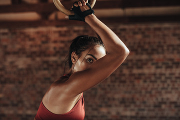 Strong woman exercising with dip rings