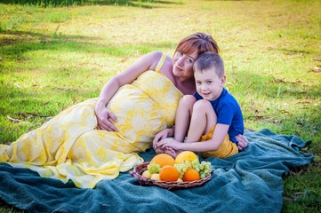 A happy beautiful Caucasian family - a pregnant young woman in a long yellow dress and her 6 year old child son on a picnic in a park eating fresh fruit. Green grass background and a dark green plaid.