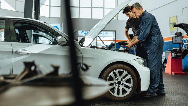 Mechanics inspecting a car using an electronic device