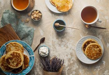 Keuken foto achterwand Bakkerij Tea, homemade pancakes, honey, cream sauce and lavender on light concrete table, romantic breakfast pancake party, various morning food, healthy lifestyle. Selective focus, top view
