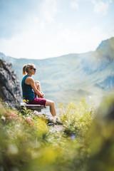 Beautiful Sportive Hiker girl having a break and relaxing on a bench near a lake enjoying the sunshine