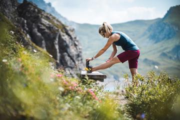 Beautiful Sportive Hiker Girl Stretching while having a break near a beautiful Alpine Lake in the Austrian Alps