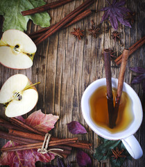 Hot drink (apple tea, sider, punch) with cinnamon stick, star anise and clove. Seasonal mulled drink on wooden background. Hot drink with apples for autumn or winter time.