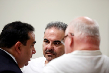 El Salvador's former President Elias Antonio Saca speaks with his lawyer during a recess at his hearing on corruption charges in San Salvador