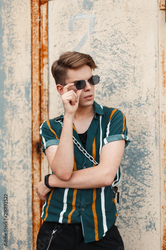 c9e2592f9f5 Young handsome stylish man with sunglasses in fashionable shirt with bag  posing near old metal wall
