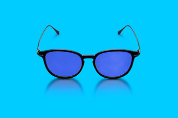 Elegant glasses made of dark plastic and metal, with dark blue glasses on a blue background