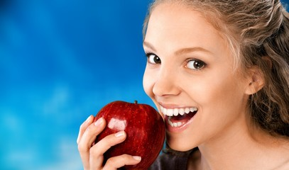 Attractive young woman holding fresh apple