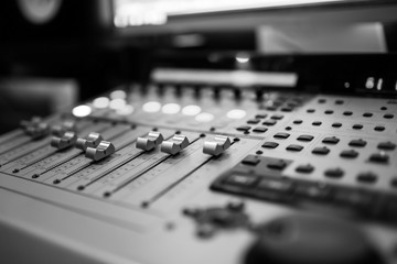 Sound recording studio mixing desk. Music mixer control panel. Closeup. Selective focus. Black and White image