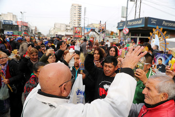A Catholic priest blesses faithfuls during the feast day of San Cayetano, the patron saint of labour and bread, outside San Cayetano church in Buenos Aires