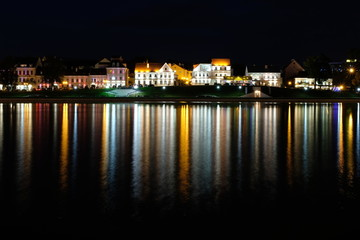 Troickoe predmeste is a picturesque old quarter on the bank of the Svisloch River in the center of Minsk. The night city is reflected in the river.