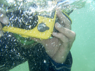 Underwater-photographer. Diver taking a photograph underwater. Ocean.