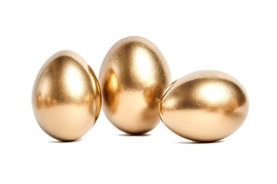 Three golden eggs isolated on white background. Conceptual image