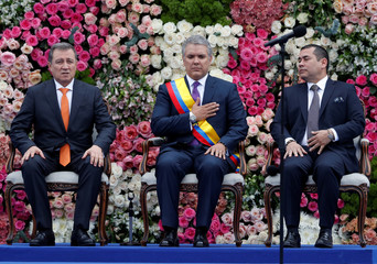Colombia's new President Ivan Duque gestures alongside the President of the Senate Ernesto Macias Tovar (L) and President of the Congress Alejandro Chacon Camargo (R) after being sworn in during his inauguration ceremony at the Bolivar Square