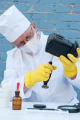 Elderly solid person in white dressing gown, cap, medical mask, glasses cleans matrix of digital camera with special means. Lens, sensor, matrix, cleaning wands, magnifier, isopropyl alcohol.
