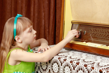 The girl turns the volume knob on the old radio. Retro style.
