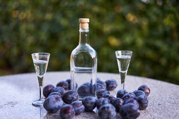 Close up picture of the bottle of homemade slivovitz or plum brandy with two glases of short drink and fresh riped plums on the stone table outdoor with soft focused background.