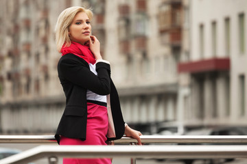 Young fashion business woman walking in city street