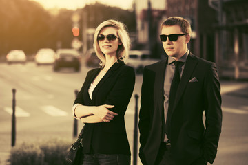 Young business couple walking in city street