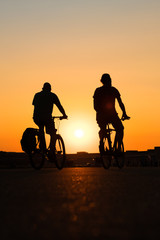 two people on bicycle with sunset sky background