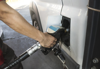 Hand refilling the car with fuel at the refuel station