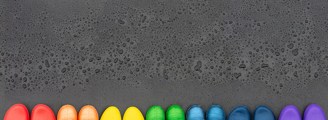 Colorful rubber boots lined with rainbow colors on the black surface in front of raindrops. Copy space.