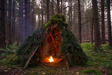Primitive Wikiup Bushcraft Survival Shelter with a campfire burning in the Forest. A traditional shelter similar to a tepee.