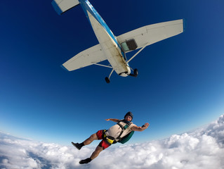 Parachutist in casual clothes jumping off the plane on a summer day