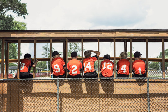 Baseball teammates in the dugout sitting on the fence