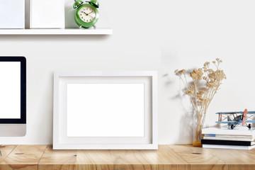 Blank poster frame on desk with supplies..Mockup design concept