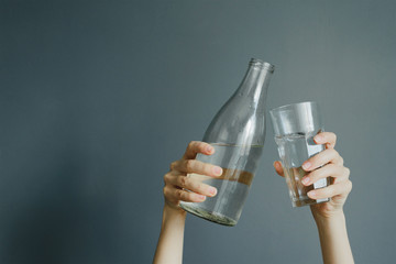 caucasian woman holds bottle with water and glass on gray background, stock photo