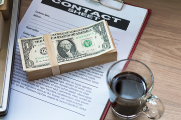 Dollar bill,black coffee,business document and contact sheet with warm morning light near the window.Copy space.