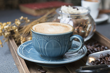 Latte cup,coffee bean,book and dried flowers jar on wooden tray with warm morning light near the window.Copy space.