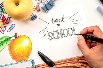 female hand drawing a lettering Back to school on illustration with white background with books and apple