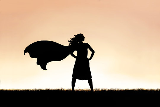 Strong Beautiful Caped SuperHero Woman Silhouette Isolated Against Sunset Sky Background