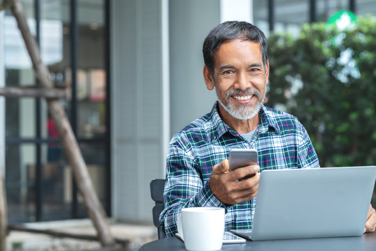 Smiling happy mature asian man with white stylish short beard using smartphone gadget serving internet at coffee shop cafe outdoor. Old indian or hispanic man using network technology with confident.