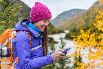Mobile young girl using technology in autumn hiking outdoor. Happy Asian woman playing smartphone games outside