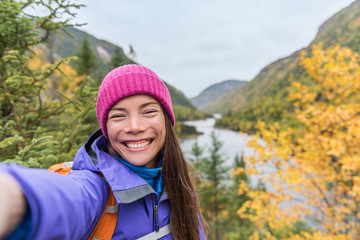 Selfie Asian girl hiking in autumn nature mountain camping outdoor fall lifestyle. Woman taking photo with mobile phone online.
