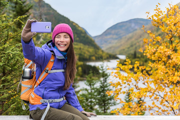 Mobile phone girl taking selfie photo on nature hike trail lifestyle. Happy Asian hiker woman holding smartphone selfie.
