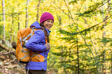 Hiking autumn woman in outdoor forest. Happy backpacker Asian girl hiker with backpack, hat, jacket, sportswear.
