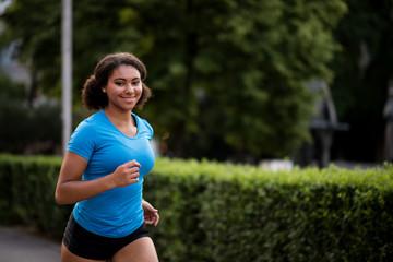 Smiling woman jogger looking at camera