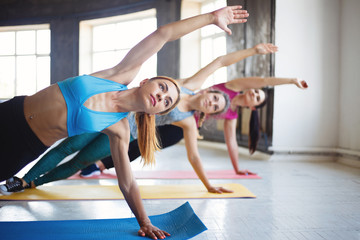 Leisure, sport, fitness, yoga class, relaxation, balance, flexibility. Fit women practicing yoga in studio.