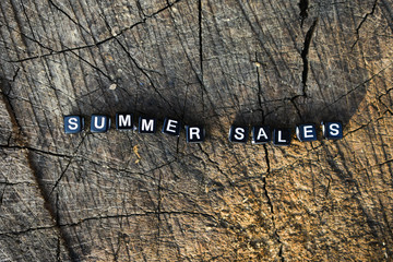 "Inscription ""summer sales"" on a wooden background"